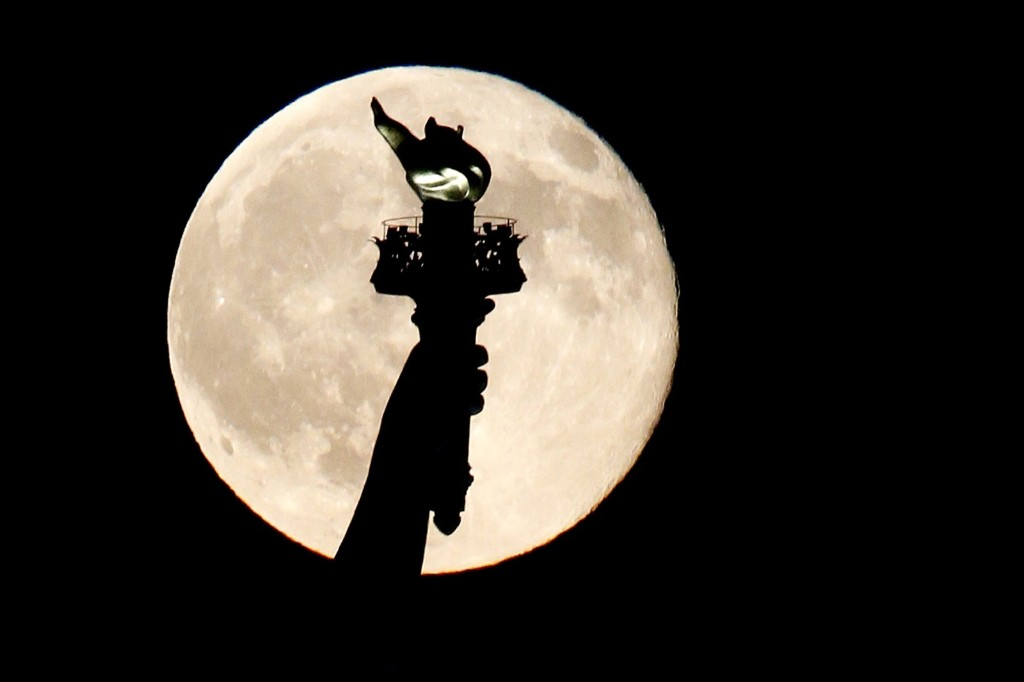 A blue moon rises behind the torch of the Statue of Liberty as seen from Liberty State Park in Jersey City, N.J. AP Photo/Julio Cortez