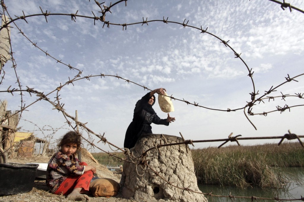 A woman bakes traditional bread as a girl sits nearby in the Chebayesh marsh, southeast of Baghdad. REUTERS/Alaa Al-Marjani