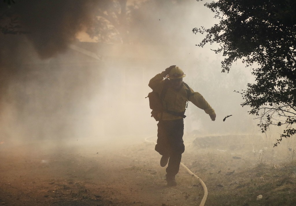 A firefighter runs away from a burning structure, Monday, July 30, 2018, in Finley, Calif. (AP Photo/Marcio Jose Sanchez)