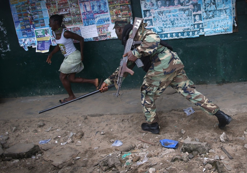 Soldier in the Ebola Task Force beats a local resident while enforcing a quarantine on the West Point slum in Monrovia, Liberia. John Moore/Getty Images