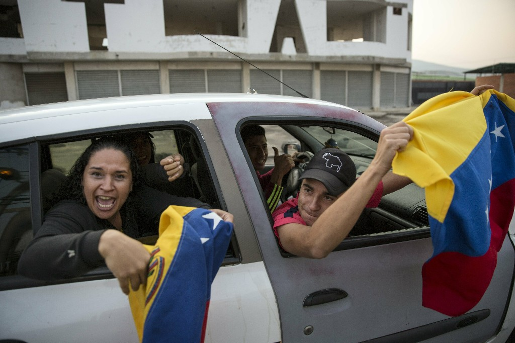 People fly Venezuelan flags and chant anti-government slogans as they drive to the Venezuela Aid Live concert that will play on the Colombian side of the border, in Urena, Venezuela, Friday, Feb. 22, 2019. Venezuela's power struggle is set to convert into a battle of the bands Friday when musicians demanding Nicolas Maduro allow in humanitarian aid and those supporting the embattled leader's refusal sing in rival concerts being held at both sides of a border bridge where tons of donated food and medicine are being stored. (AP Photo/Rodrigo Abd)