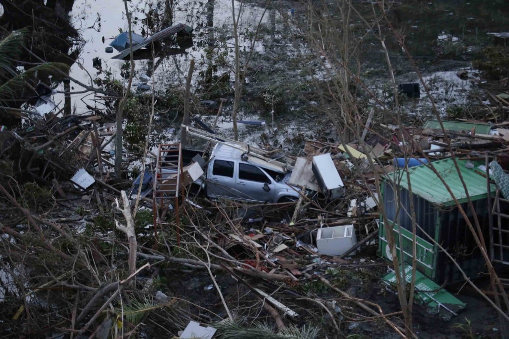 A vehicle lies amid debris caused by powerful typhoon Haiyan that hit Tacloban city, in Leyte province in central Philippines. AP Photo/Bullit Marquez