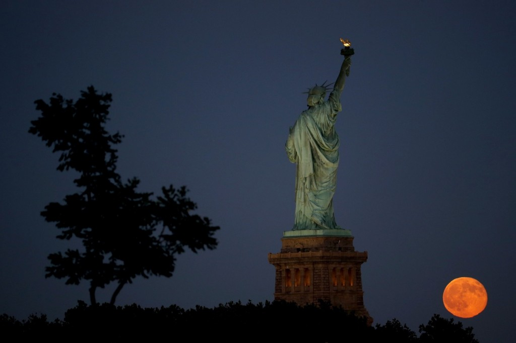 A blue moon rises behind the Statue of Liberty as seen from Liberty State Park in Jersey City, N.J. AP Photo/Julio Cortez
