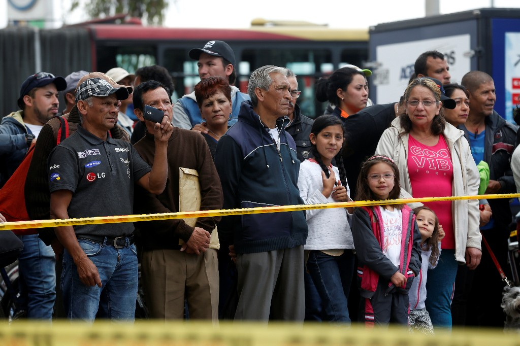 People stand beside a security tape set up close to the scene where a car bomb exploded, according to authorities, in Bogota, Colombia January 17, 2019. REUTERS/Luisa Gonzalez