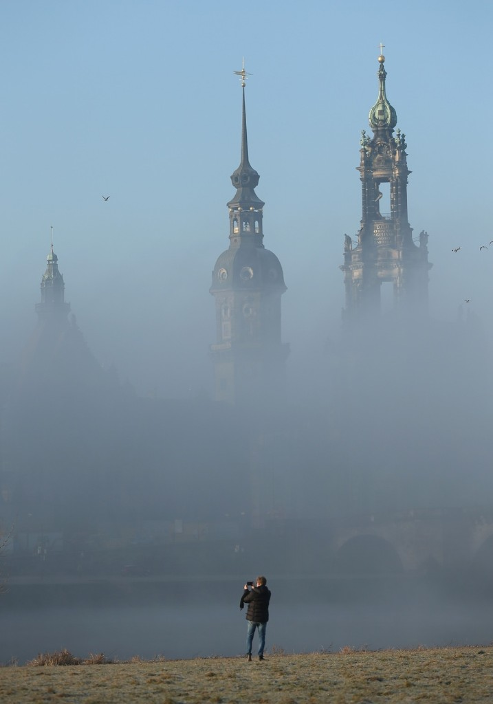Fog rising from the Elbe River shrouding the towers of the Residenzschloss Dresden palace and the Catholic Hofkirche church in Dresden. Sean Gallup/Getty Images