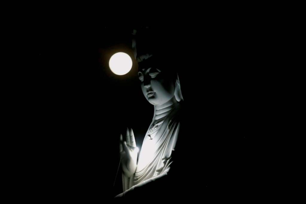 The full moon behind a Buddha statue during the Vesak Day celebrations at Duoc Thuong pagoda in Hanoi. REUTERS/Kham