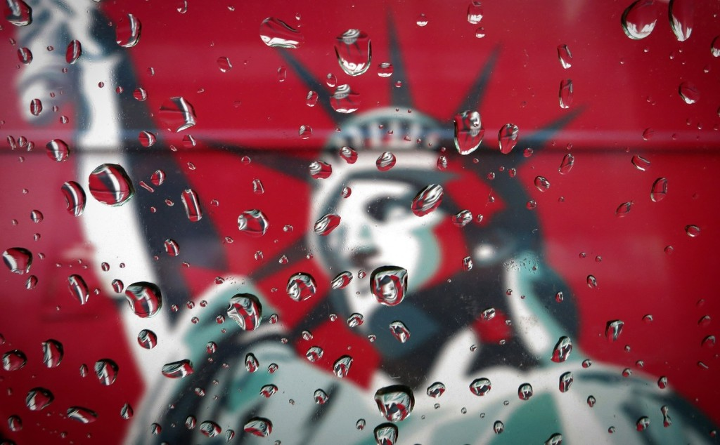An image of the Statue of Liberty is seen though a rain-covered taxi window in New York. REUTERS/Carlo Allegri
