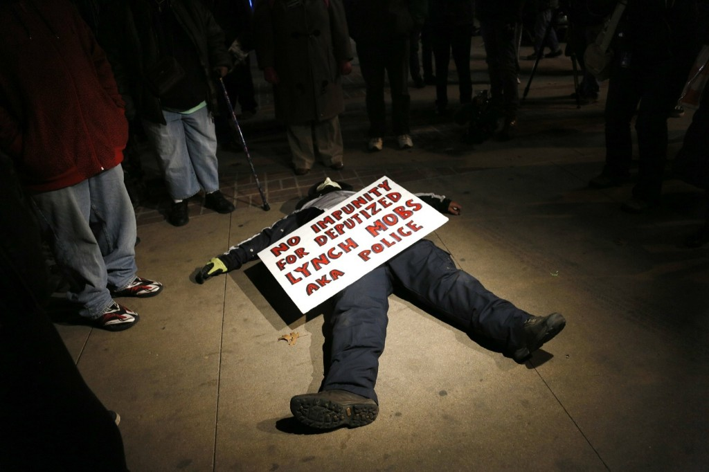 A protester lies on the sidewalk in downtown Denver. REUTERS/Rick Wilking