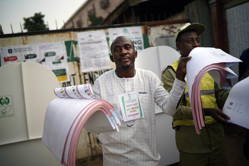 Nigerian election officials display ballots to the public as people line up to cast their vote in Kaduna, Nigeria, Saturday Feb. 23, 2019. Incumbent President Muhammadu Buhari is to face opposition presidential candidate Atiku Abubakar in the presidential election. (AP Photo/Jerome Delay)