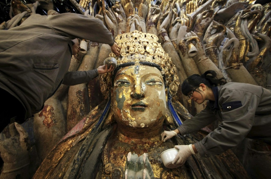 Workers peel off loose gold foil as part of a restoration project for an 800-year-old Thousand-Hand Guanyin Buddhist statue on Mount Baoding in China. The stone-carving statue dates back to the Southern Song Dynasty (1127-1279). REUTERS/Stringer