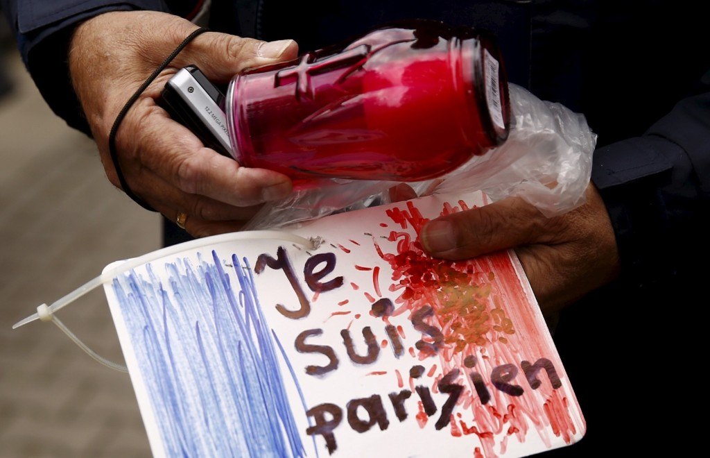 "A man holds a candle and a drawing depicting the French flag carrying the words ""I am Parisian"" in front of the French embassy in Warsaw. REUTERS/Kacper Pempel"