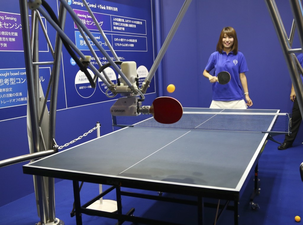 A model plays ping-pong with OMRON Corp.'s three-legged robot during the CEATEC Japan advanced technologies show in Chiba. AP Photo/Koji Sasahara