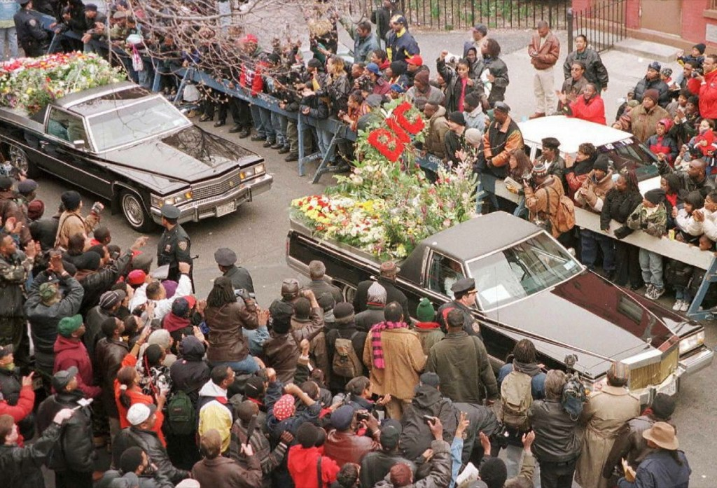 Funeral cars filled with floral tributes to rapper Biggie Smalls pass down St James Place, the street in Brooklyn where his mother lives, in a fairwell drive-by for the Brooklyn native, March 1997. JON LEVY/AFP/Getty Images