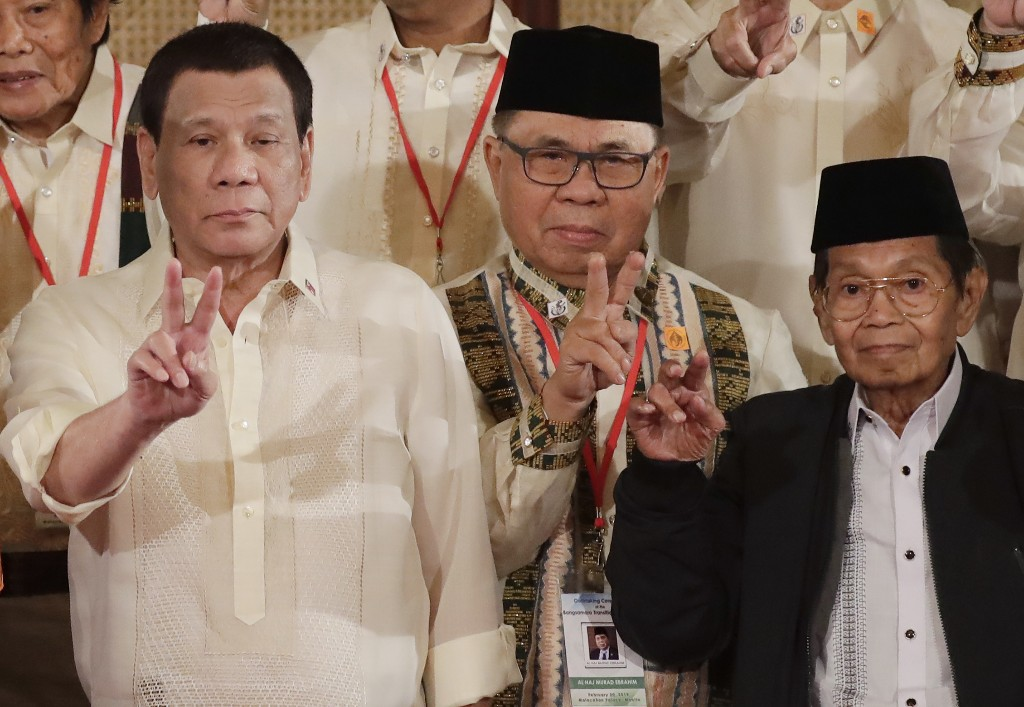 President Rodrigo Duterte, left, Murad Ebrahim, Chairman of the Moro Islamic Liberation Front, and Ghazali Jaafar, Vice-chair for Political Affairs and Chair of the Bangsamoro Transition Commission, flash the peace sign following oath-taking ceremony for the creation of the Bangsamoro Transition Authority or BTA at the Presidential Palace in Manila, Philippines Friday, Feb. 22, 2019. The Muslim rebels will serve as administrators of a new Muslim autonomous region in a delicate milestone to settle one of Asia's longest-raging rebellions. Several commanders, including Commander Bravo, long wanted for deadly attacks were given safety passes to be able to travel to Manila and join the ceremony. (AP Photo/Bullit Marquez)