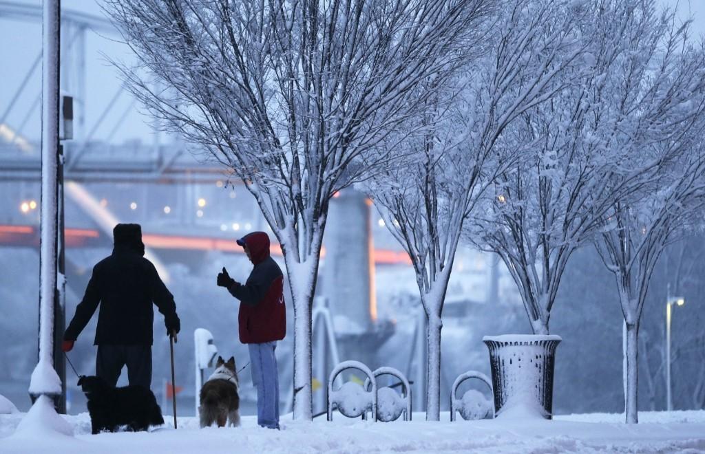 Neighbors Steve Turner, left, and Mac McDonald take their dogs for an evening walk in the snow Friday, in Nashville, Tenn. AP Photo/Mark Humphrey