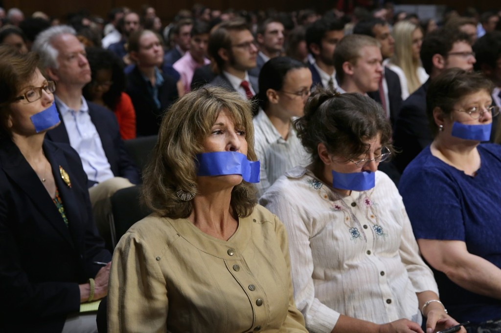 Four women wear blue tape over their mouths as a silent protest during Senate Judiciary Committee hearing about political donations and freedom of speech. Chip Somodevilla/Getty Images