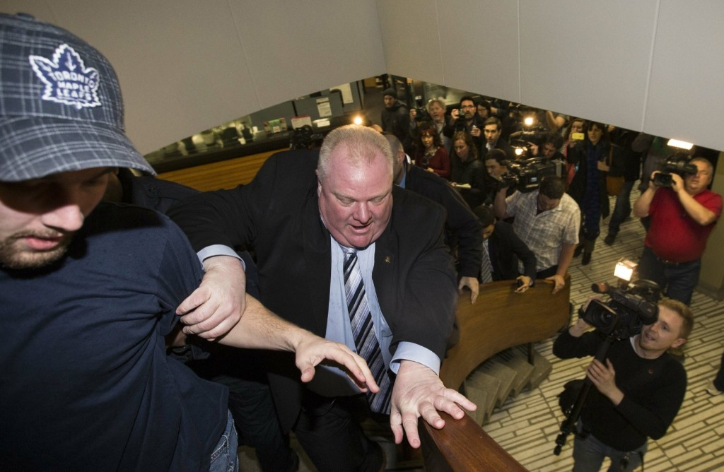 Toronto Mayor Rob Ford runs from cameras after he was caught up in fresh controversy Monday. A new video showed him agitated and apparently swearing outside city hall. REUTERS/Mark Blinch