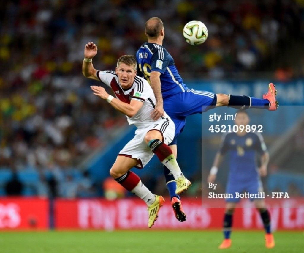 Bastian Schweinsteiger of Germany and Rodrigo Palacio of Argentina compete for the ball. Shaun Botterill/FIFA/Getty Images