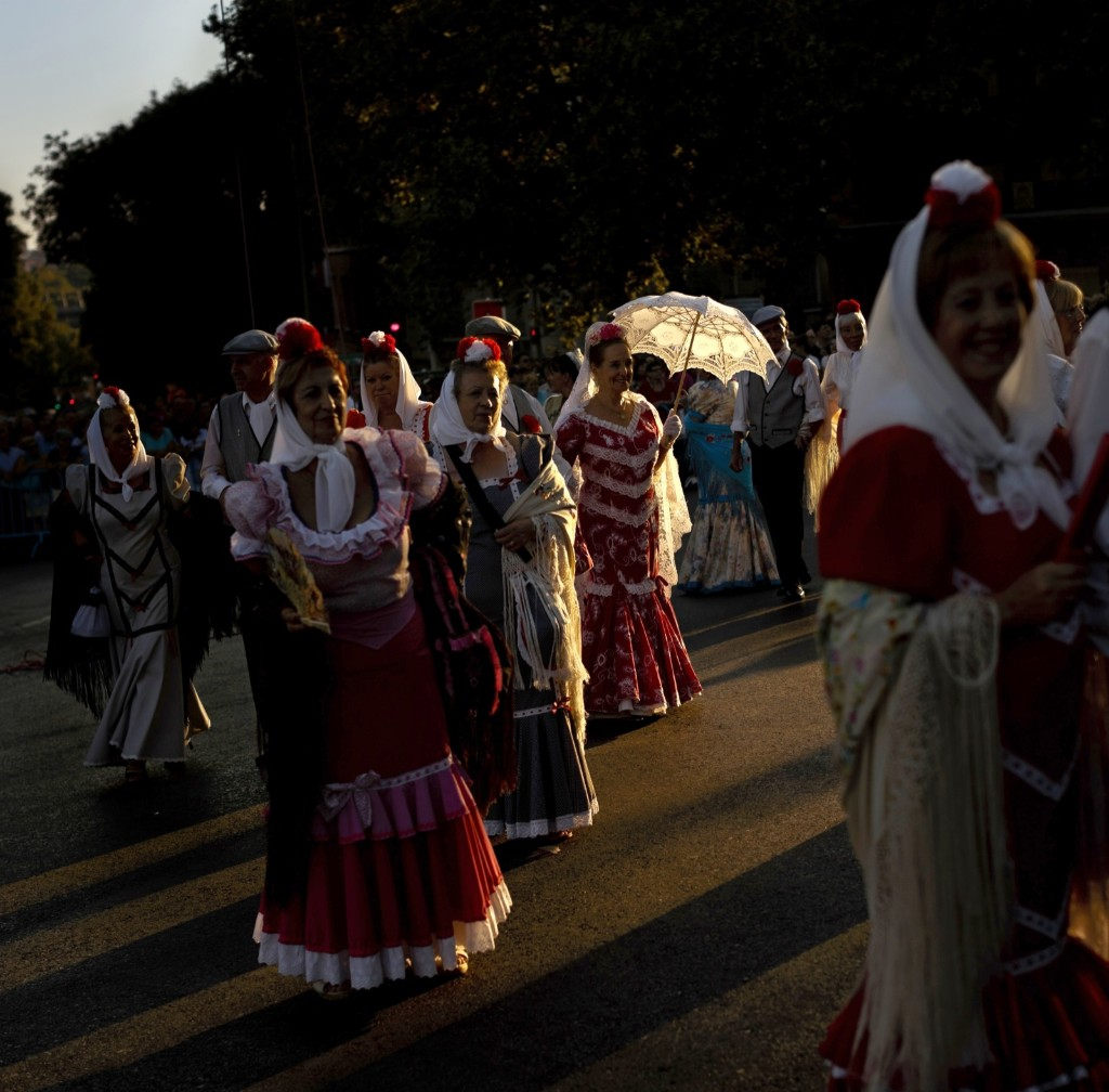 Women dressed with 'mantillas' and men with 'Chulapos' outfits during the Nuestra Senora de la Paloma procession in Madrid. AP Photo/Daniel Ochoa de Olza