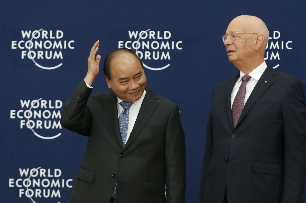 Vietnam's Prime Minister Nguyen Xuan Phuc, left, and World Economic Forum's founder and executive chairman Klaus Schwab wait for the arrival of guests to the World Economic Forum on ASEAN at the Convention Center in Hanoi, Vietnam, Wednesday, Sept. 12, 2018. (Kham/Pool Photo via AP)