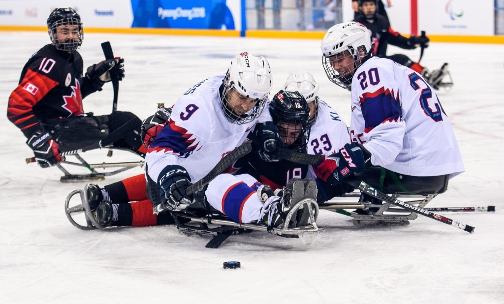 Morten Vaernes of Norway, Dom Cozzolino of Canada and Jan Roger Klakegg and Martin Hamre of Norway battle for the puck during the ice hockey preliminary round. Thomas Lovelock for OIS/IOC
