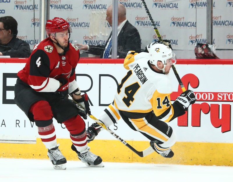 Jan 18, 2019; Glendale, AZ, USA; Pittsburgh Penguins left wing Tanner Pearson (14) is tripped by Arizona Coyotes defenseman Niklas Hjalmarsson (4) in the third period at Gila River Arena. Mandatory Credit: Mark J. Rebilas-USA TODAY Sports