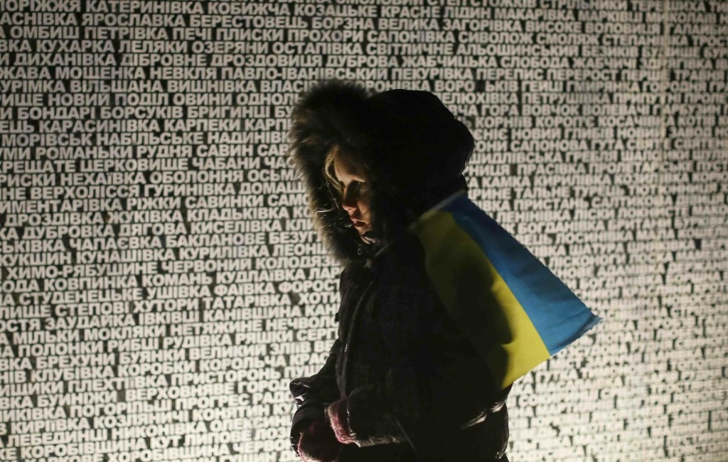 A girl stands at a monument with inscriptions of the locations that suffered during the Holodomor famine in Kiev. REUTERS/Gleb Garanich