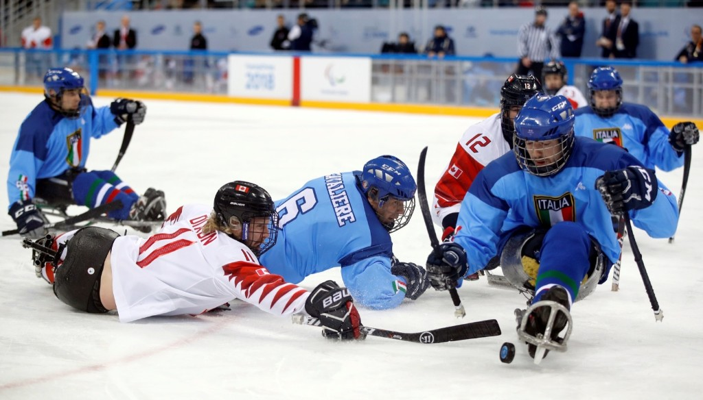 Adam Dixon of Canada and Gian Luca Cavaliere of Italy during ice hockey game at the Gangneung Hockey Centre. REUTERS/Carl Recine