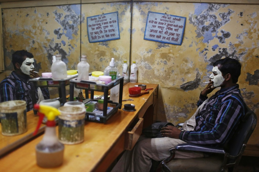A migrant laborer, his face covered with facial cream, at a barber shop in New Delhi, Monday. REUTERS/Anindito Mukherjee