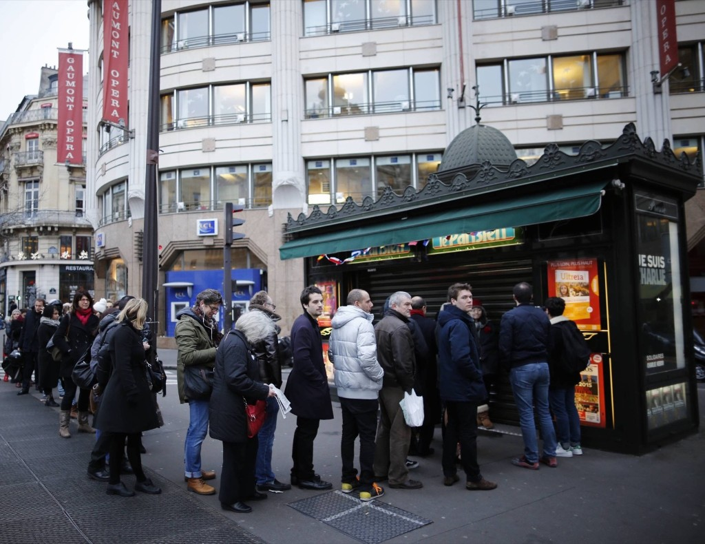People line up to get a copy of the satirical French magazine, Charlie Hebdo at a news kiosk in Paris, Wednesday. REUTERS/Stephane Mahe