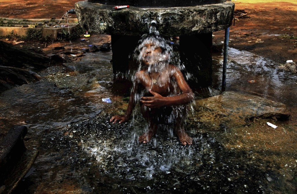 An Indian boy takes bath under a roadside public water supply tap on a hot afternoon in Bhubaneswar. AP Photo/Biswaranjan Rout