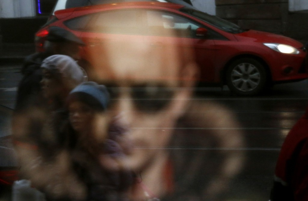 A reflection in a shop window with a T-shirt bearing an image of Russian President Vladimir Putin in St. Petersburg. REUTERS/Alexander Demianchuk