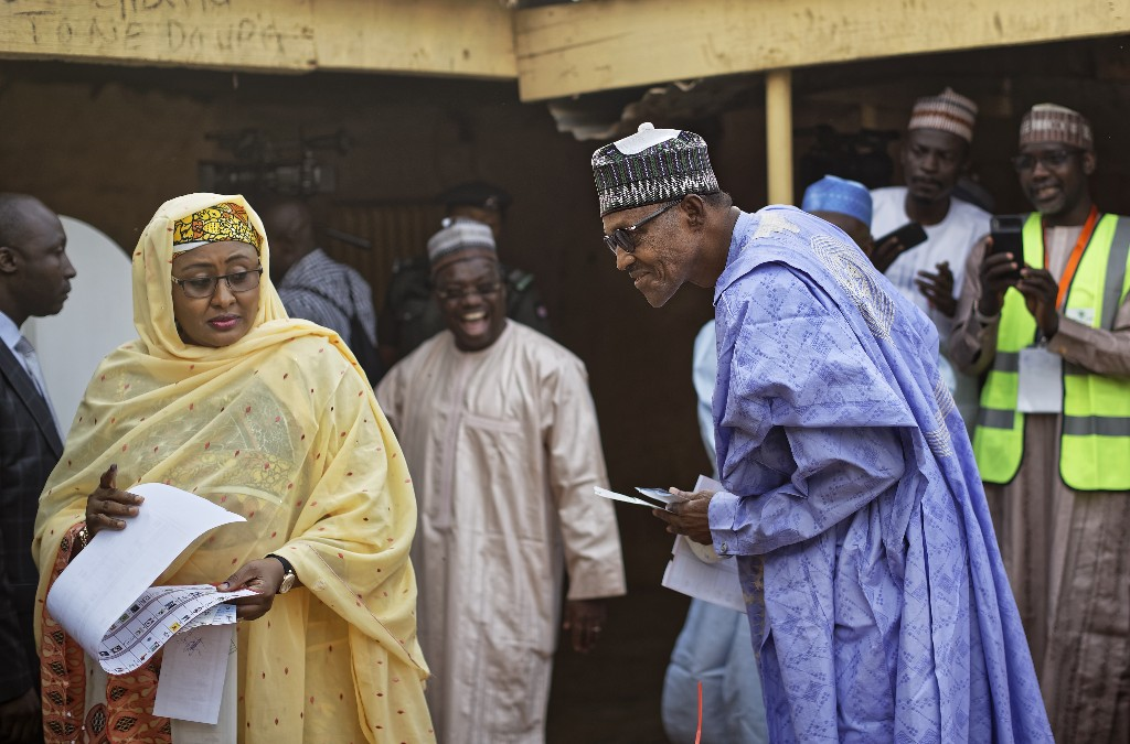 Nigeria's President Muhammadu Buhari jokingly looks across at the ballot paper of his wife Aisha, left, to see who she has voted for, before casting his vote in his hometown of Daura, in northern Nigeria Saturday, Feb. 23, 2019. Nigerians are going to the polls for a presidential election Saturday, one week after a surprise delay for Africa's largest democracy. (AP Photo/Ben Curtis)