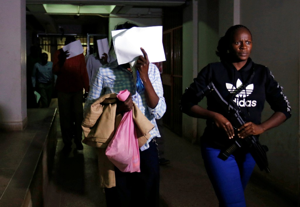 Gladys Kaari covers her face as she is escorted from the Mililani Law Courts where she appeared as a suspect in connection with the attack at the DusitD2 complex, in Nairobi, Kenya January 18, 2019. REUTERS/Thomas Mukoya