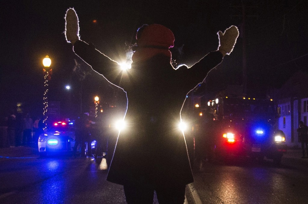 A female protester raises her hands while blocking police cars in Ferguson, Nov. 25. REUTERS/Adrees Latif