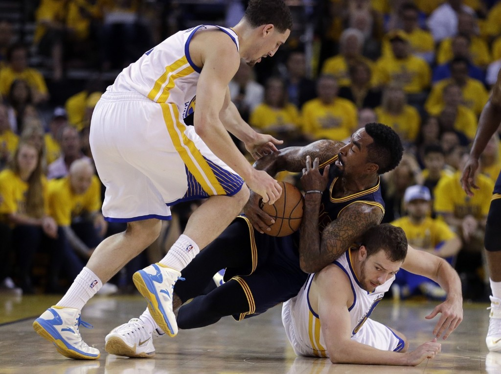 Cavaliers J.R. Smith tries to control the ball between Klay Thompson, top, and forward David Lee. AP Photo/Ben Margot