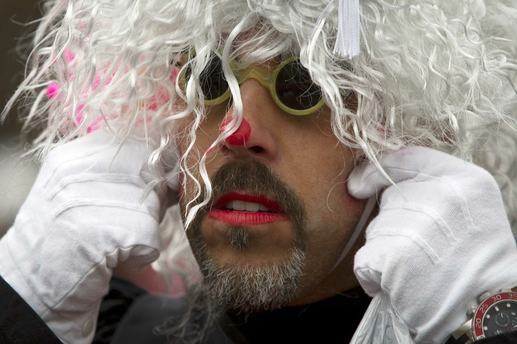 A clown adjusts his wig as he gets ready to participate. REUTERS/Carlo Allegri