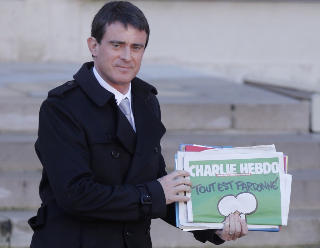 French Prime Minister Manuel Valls holds a copy of Charlie Hebdo as he leaves a weekly cabinet meeting at the Elysee Palace in Paris, Wednesday. REUTERS/Christian Hartmann