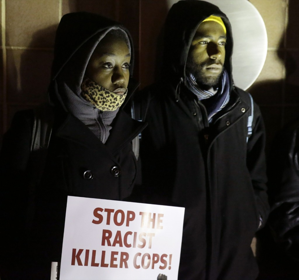 Monet Felton, left, and Jo Schaffer gather outside the Chicago Police headquarters just before the announcement of the grand jury decision. AP Photo/Charles Rex Arbogast