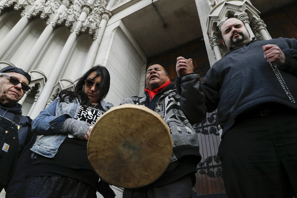Native American protestors hold hands with parishioner Nathanial Hall, right, during a group prayer outside the Catholic Diocese of Covington Tuesday, Jan. 22, 2019, in Covington, Ky. The diocese in Kentucky has apologized after videos emerged showing students from Covington Catholic High School mocking Native Americans outside the Lincoln Memorial on Friday after a rally in Washington. (AP Photo/John Minchillo)