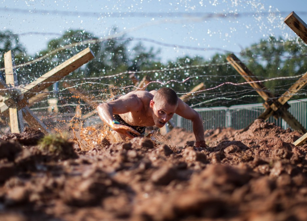 Hobie Call crawls under barbed wire in 15k race at the inaugural Battlefrog Obstacle Course Series in Conyers, Ga. The course was designed by Navy SEALs. AP Photo/Branden Camp