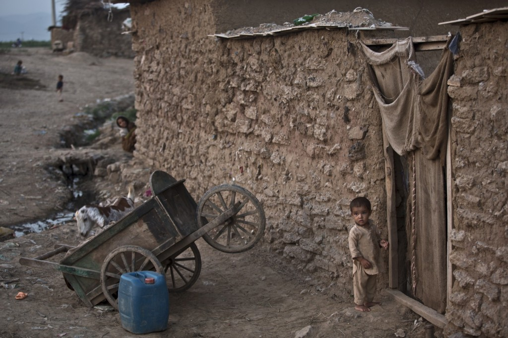 An Afghan refugee stands at the doorway of his family's mud house on the outskirts of Islamabad. AP Photo/Muhammed Muheisen