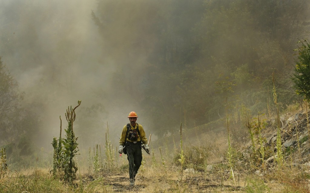A firefighter walks away from a smoke-filled hillside while fighting the First Creek Fire near Chelan, Wash. AP Photo/Ted S. Warren