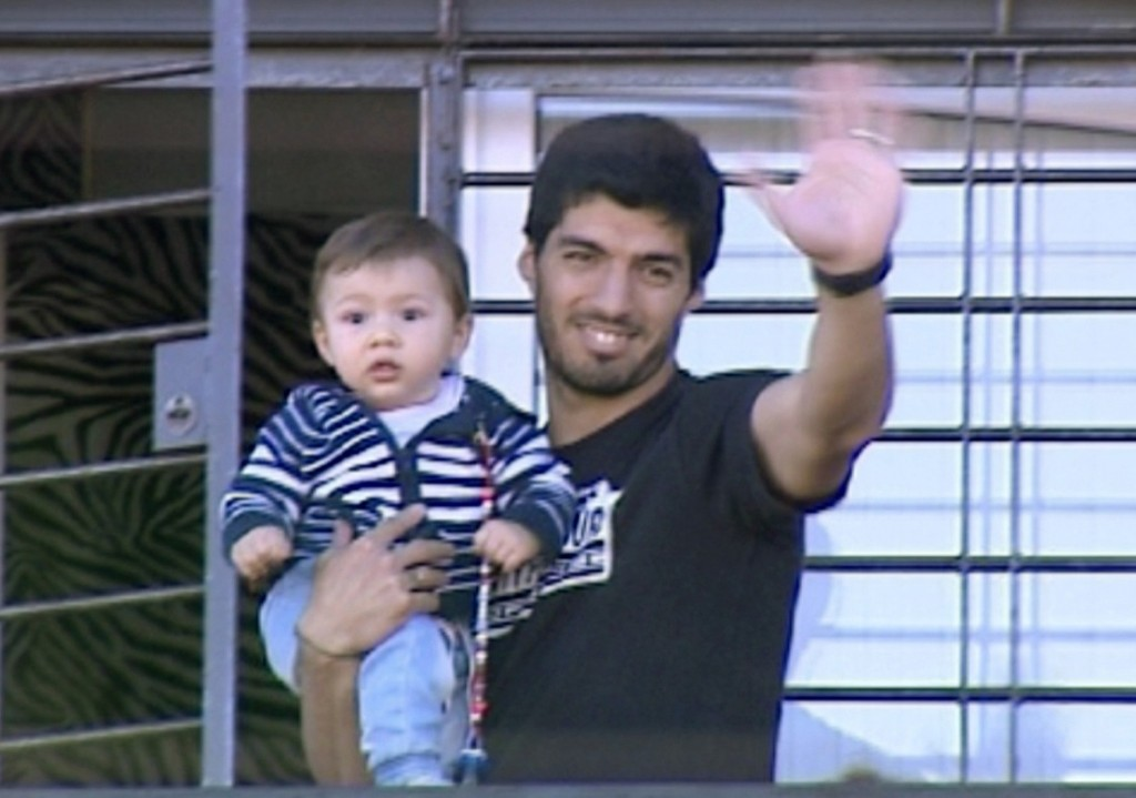 Suspended Uruguayan striker Luis Suarez with his son Benjamin at his house on the outskirts of Montevideo. Uruguay missed his offense today. REUTERS/Television Nacional Uruguay/Reuters TV