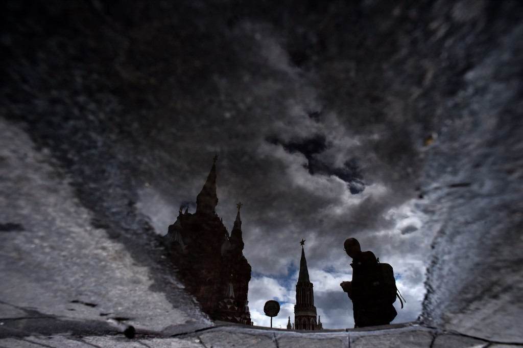 A man is reflected in a puddle as he walks across Moscow's Red Square. KIRILL KUDRYAVTSEV/AFP/Getty Images