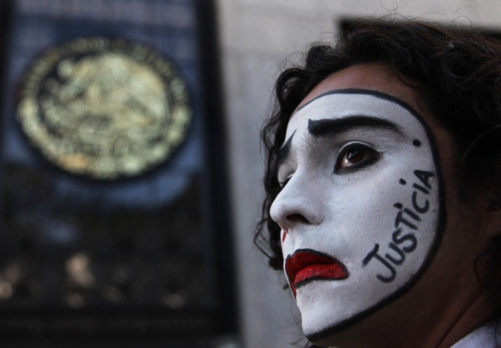 "A student wearing clown makeup with the Spanish word for ""justice"" written on the side of his face stands outside the Attorney General's office in Mexico City. AP Photo/Marco Ugarte"