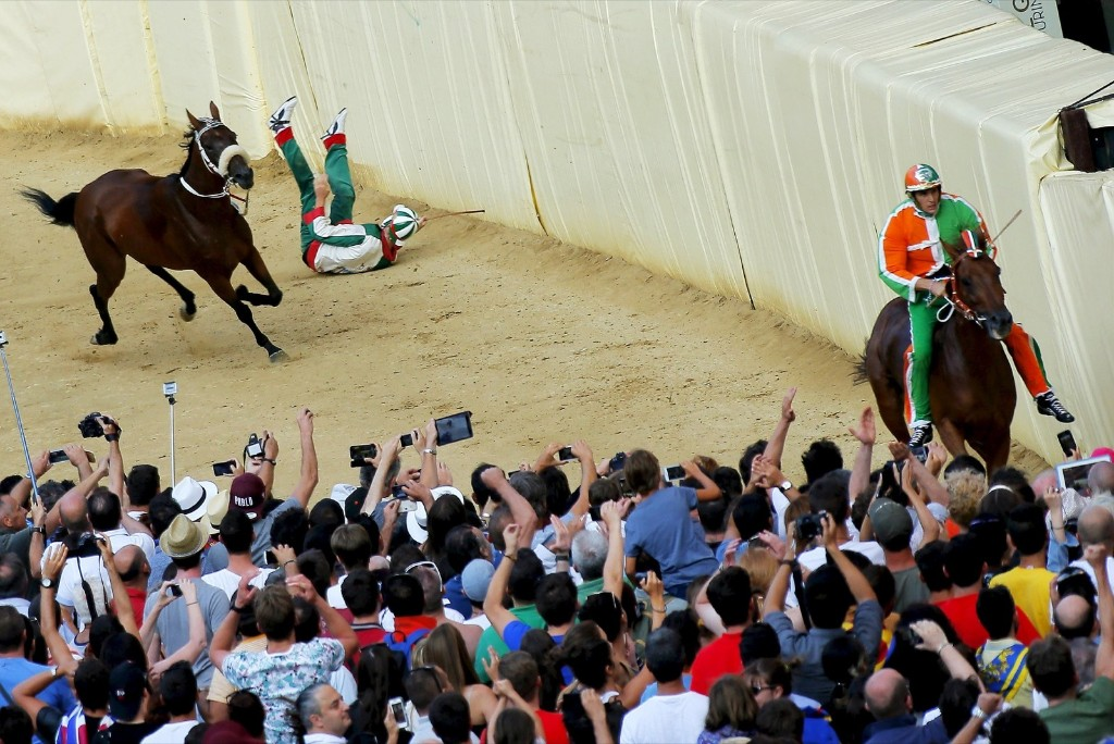 "Jockey Enrico Bruschelli of ""Oca"" (Duck) parish crashes during the Palio di Siena horse race in Siena August 17. REUTERS/Fabio Muzzi"