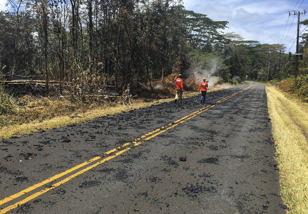 In this Sunday, May 6, 2018 photo provided by the U.S. Geological Survey, USGS scientists monitoring the eruption of Kilauea volcano in Leilani Estates walk past spatter that erupted from a fissure on Leilani Avenue, in the Leilani Estates subdivision near Pahoa on the island of Hawaii. Kilauea volcano has destroyed more than two dozen homes since it began spewing lava hundreds of feet into the air last week, and residents who evacuated don't know how long they might be displaced. The decimated homes were in the Leilani Estates subdivision, where molten rock, toxic gas and steam have been bursting through openings in the ground created by the volcano. (U.S. Geological Survey via AP)