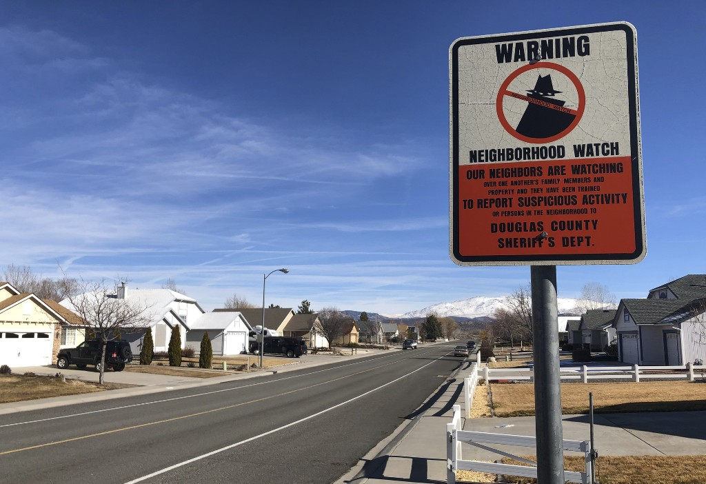 A neighborhood watch sign is seen Wednesday, Jan. 23, 2019, near the Gardnerville Ranchos, Nev., home of Connie Koontz, the first of two women in the community who were found dead in their homes. The killings of the two women and a couple north in Reno that police say were committed by a man in the U.S. illegally have put the community on edge. (AP Photo/Michelle L. Price)