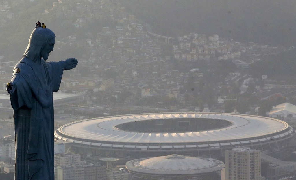 Men work on repairs on Christ the Redeemer with the Maracana in the background. REUTERS/Ricardo Moraes